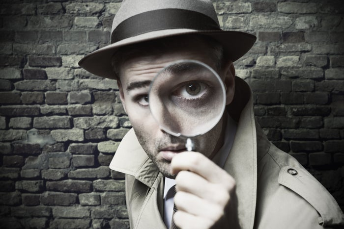 Detective looking at camera through magnifying glass.