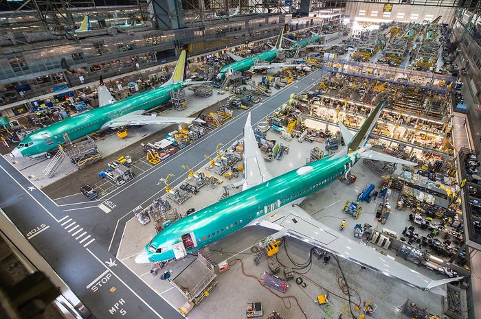 Large hangar with three Boeing aircraft and various exhibits.