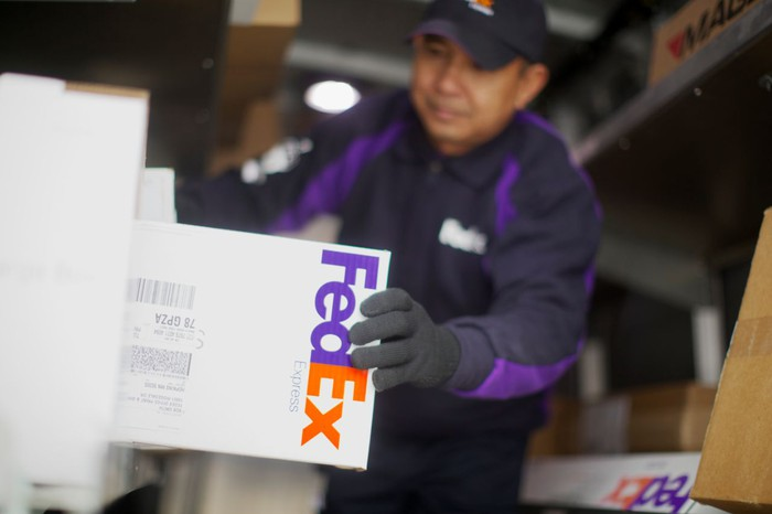 A FedEx worker handling a package in a delivery truck.