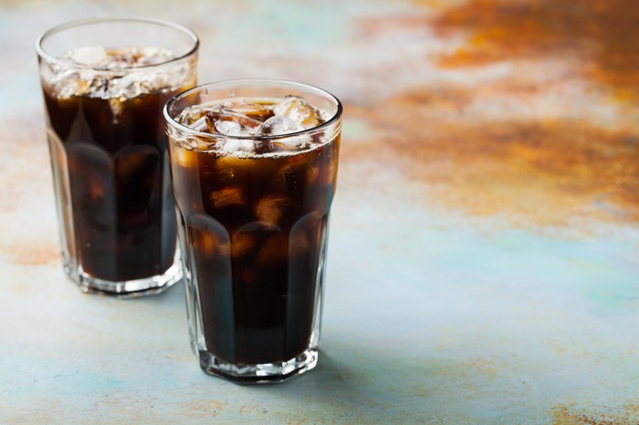Two cups of cola-style soda and ice.