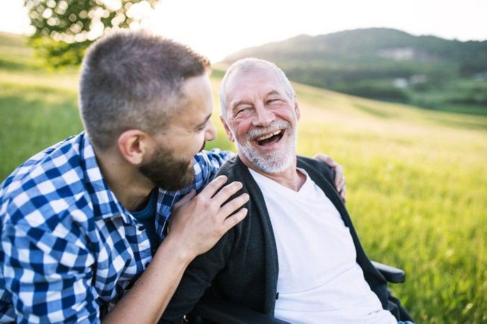 Young man putting arms around smiling older man out in a field