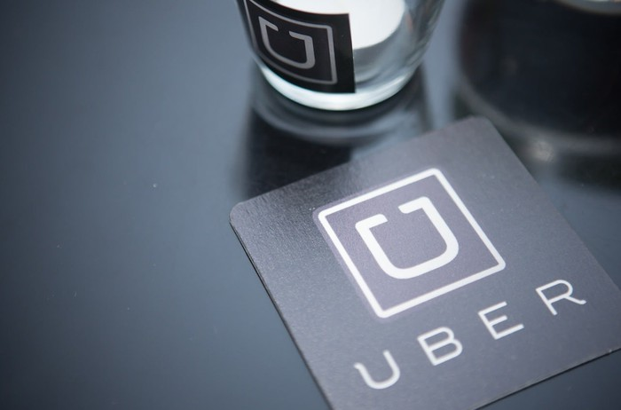 Old Uber logo on a coaster and glass on a dark table.