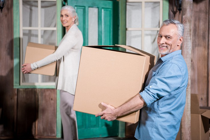 Senior man and woman carrying moving boxes