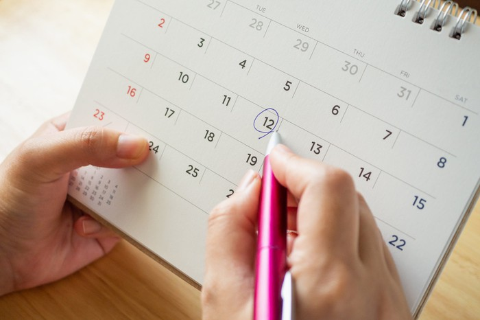 A person circling a date on a calendar with a pen.