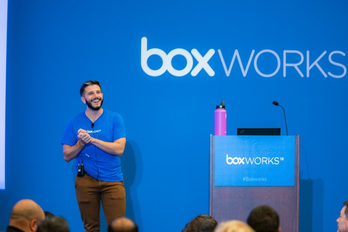 Man on stage in front of a crowd, with Box Works logo behind and on podium.