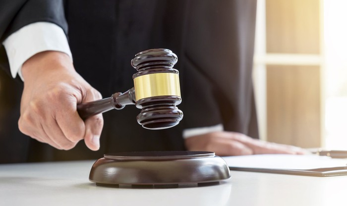 A person in judge's robes banging a gavel.