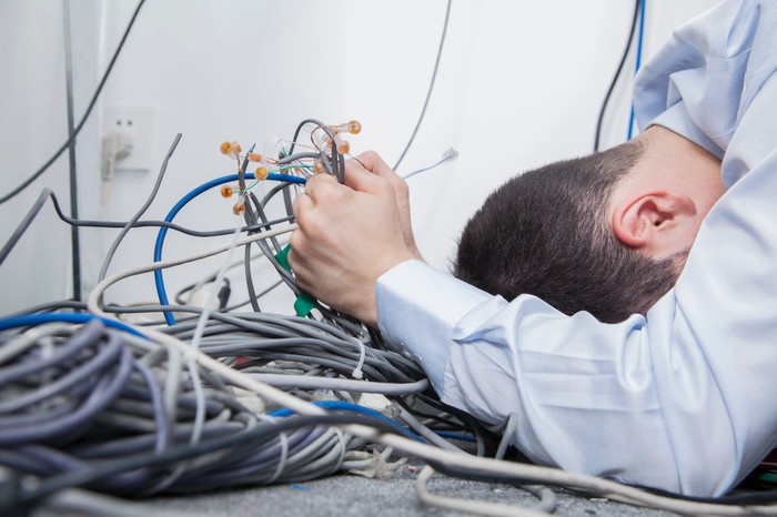 A despairing young man grabs a pile of tangled network cables, his face to the floor.