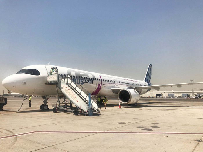 An Airbus A321LR parked on a tarmac, with air-stairs attached.