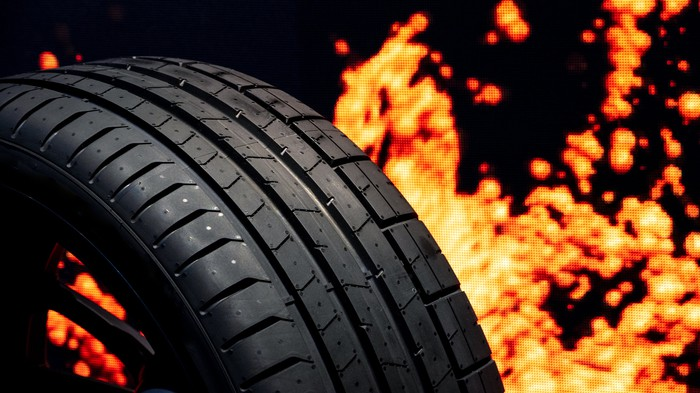 Close-up shot of a car tire, which appears to be on fire.