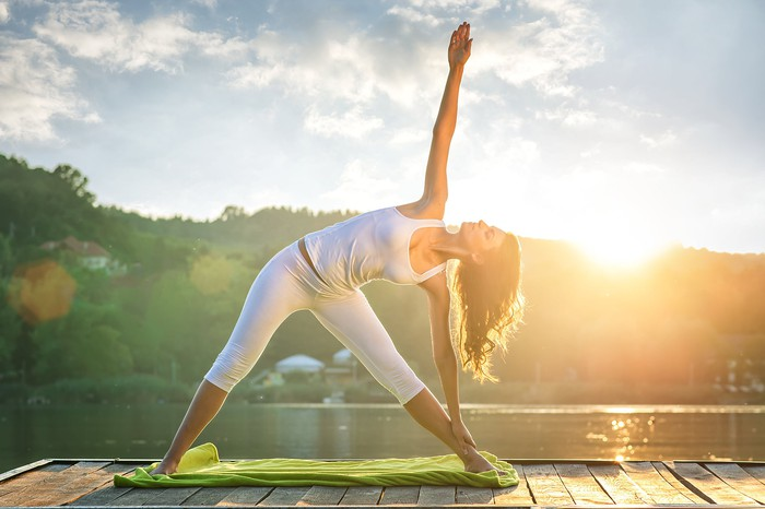 A woman holds a Triangle yoga pose in front of a rising sun.