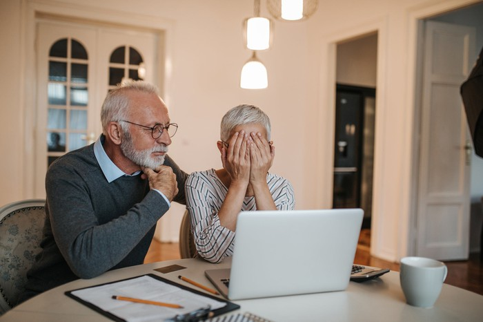 Senior couple sitting at a table in their home and looking at a laptop, as the woman covers her face.