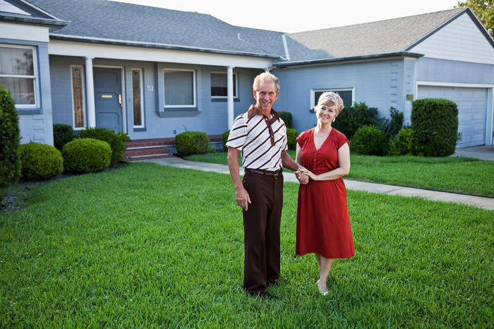 Senior couple standing on front lawn outside home