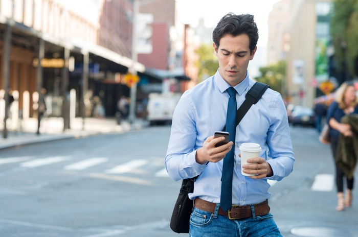 A young man looking at his phone on the street.