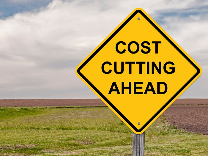 A yellow sign that reads cost cutting ahead.