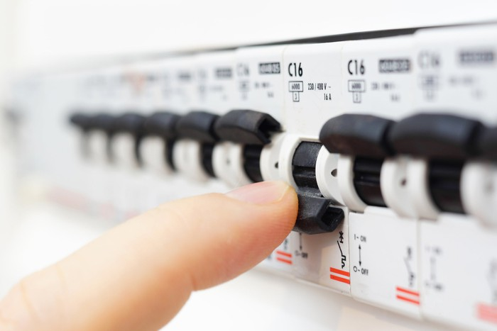 A finger atop a fuse switch in a fuse box.