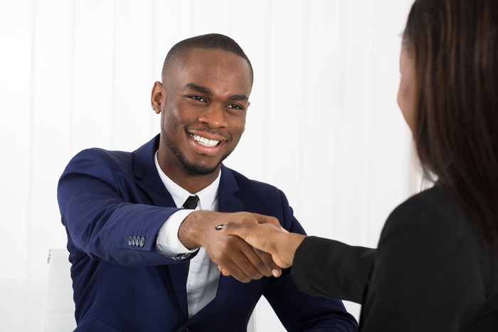 Man in suit smiling and shaking hands with woman.