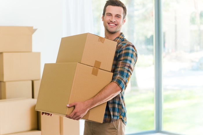 Smiling young man holding moving boxes