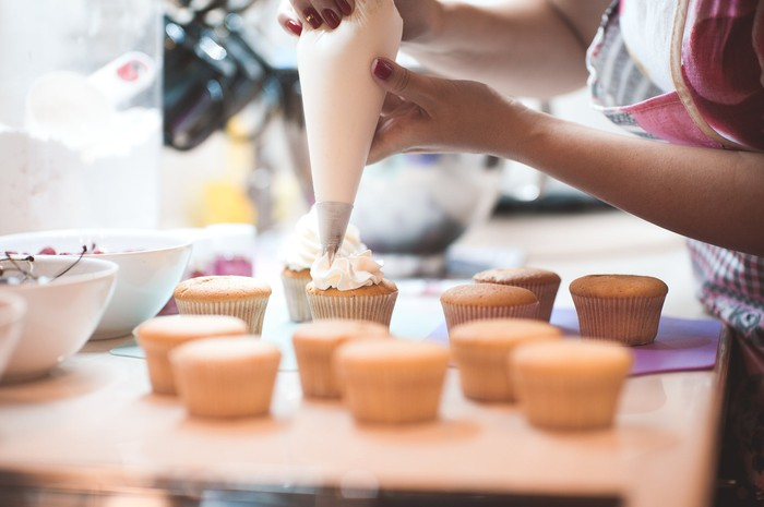 Woman frosting cupcakes