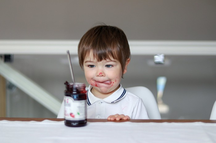 Child sitting at a table, with jelly jar in front of him and jelly smeared all over his face.