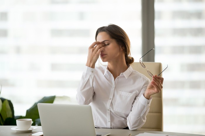 Woman in collared shirt at a laptop holding her face as if tired