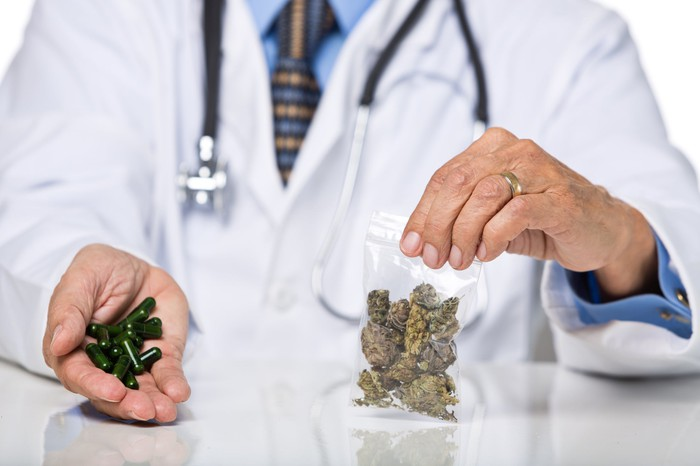A doctor with a stethoscope around his neck holding a baggie of cannabis in his left hand and cannabis-oil-filled capsules in his right hand.