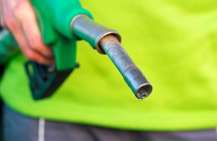 A hand holding a green diesel pump.