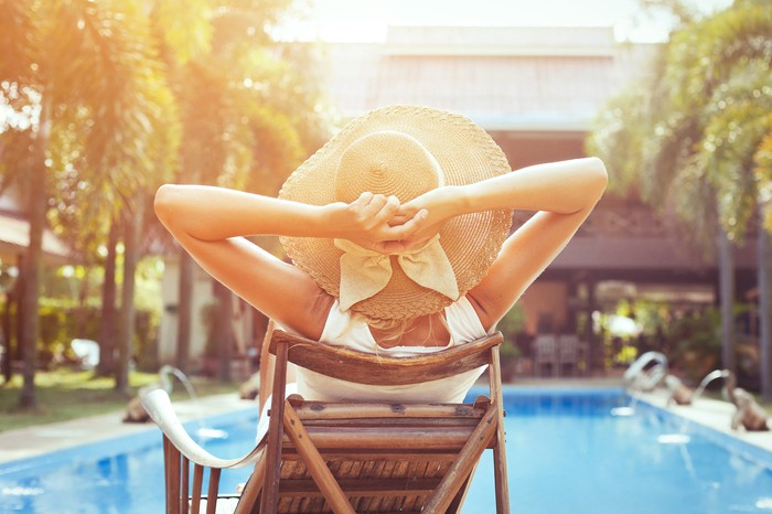 A woman relaxing at the edge of a hotel pool.