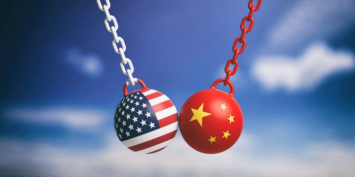 Two wrecking balls, adorned with American and Chinese flags, colliding in midair.