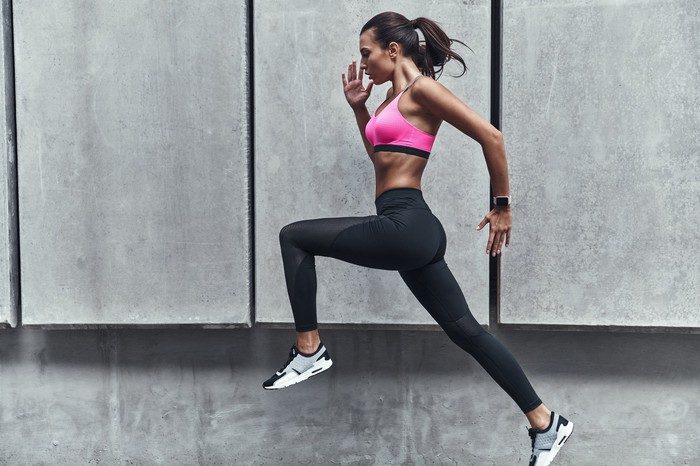 A woman exercising in front of a gray concrete wall.