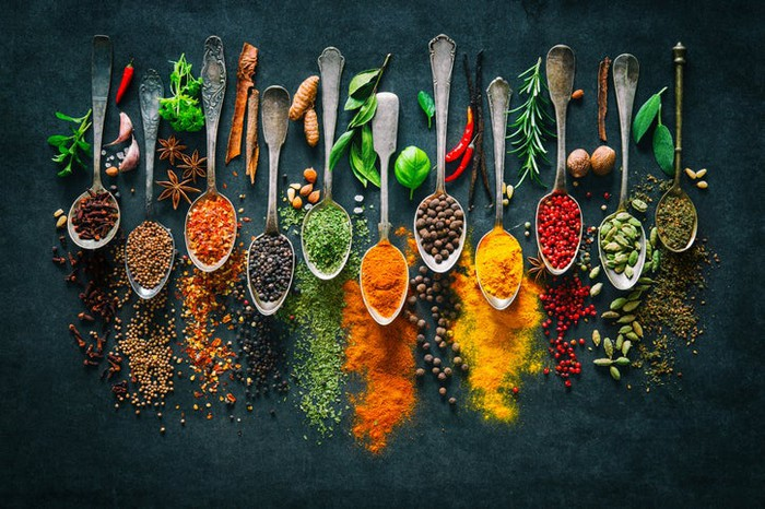 Ten spoons filled with different spices.