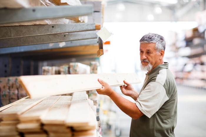 A man selecting a piece of lumber at a home-improvement store.