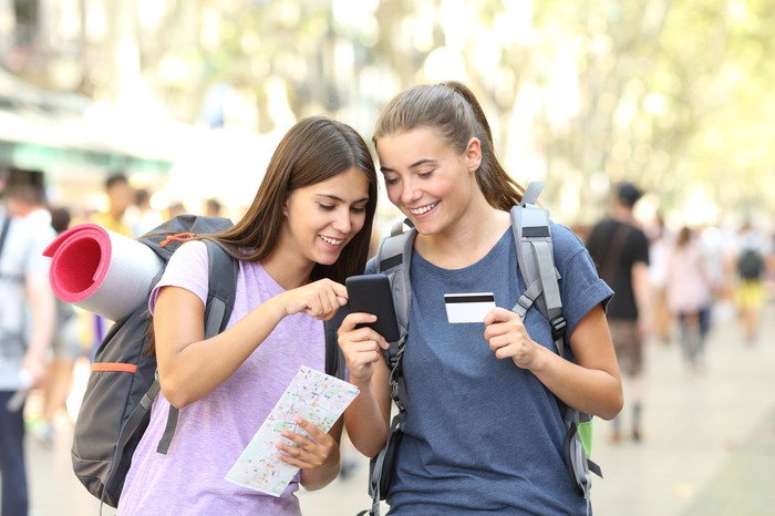 Two young women with backpacks hold credit cards and look at one's smartphone.