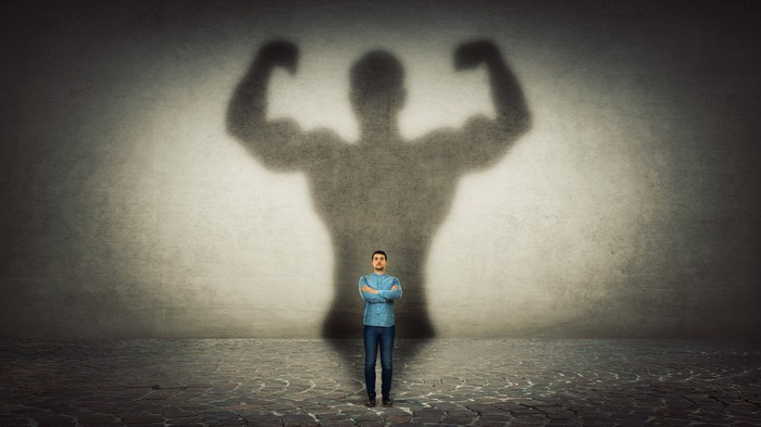 A thin man stands with his arms crossed in front of a huge, muscular shadow behind him that's three times his size.