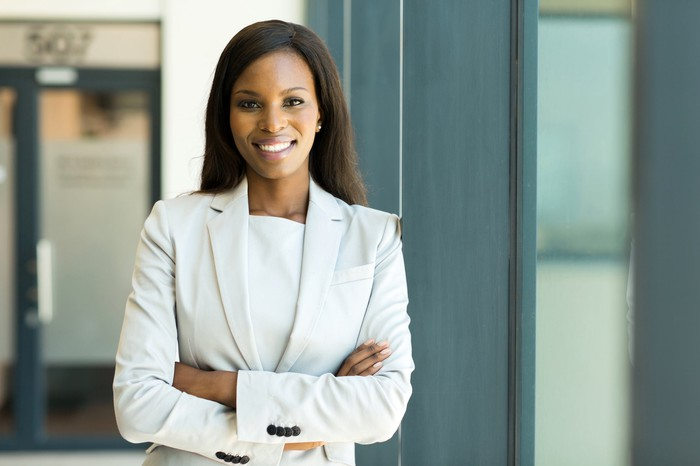 Smiling woman in business suit standing with arms crossed