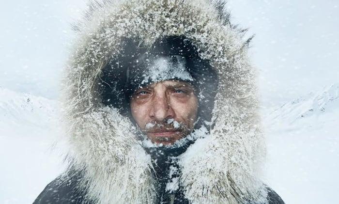 A frozen man wearing a fur-lined hood in a wintry scene.