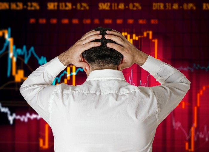 A man in a white shirt stands with his back to us and his hands on his head, looking at a crashing stock chart.