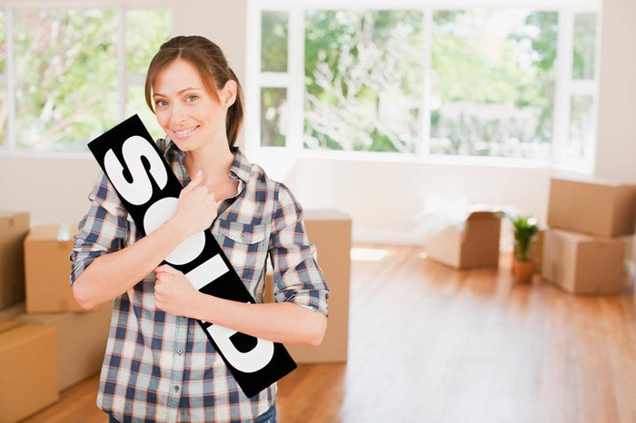 """Young woman cradling a """"sold"""" sign in her arms while standing in a room that's empty except for many boxes."""
