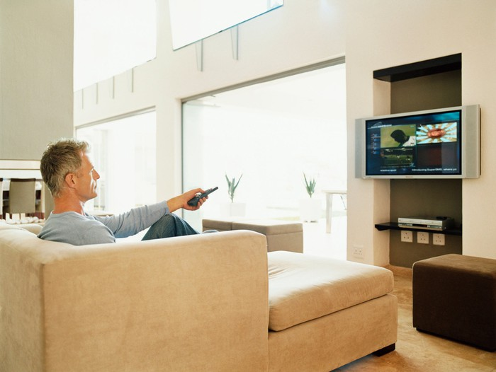 A man on a couch pointing a remote at a television.