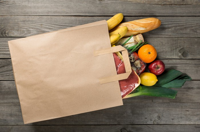 A brown paper bag full of groceries spilling out on a wood table.