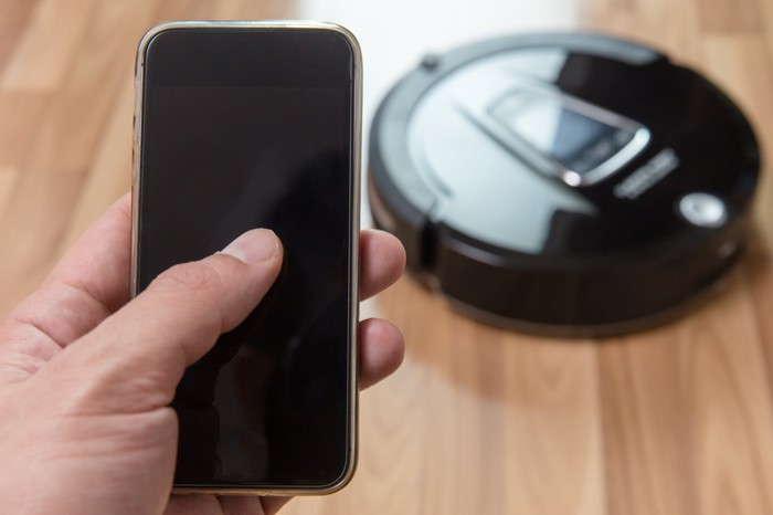 A robotic vacuum being controlled by a hand touching a smartphone.