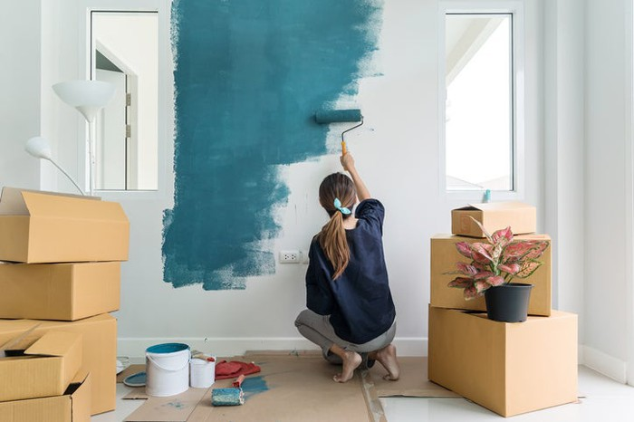 A woman painting a room in a house.