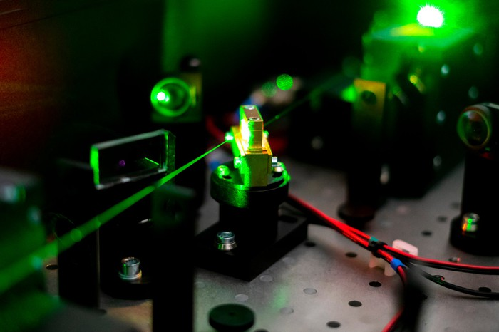 A green laser beam shines through an array of electronic circuits