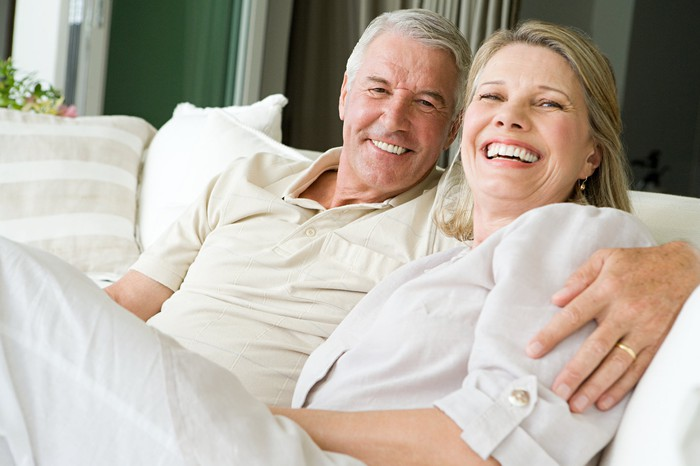 Older couple smiling, sitting on a sofa.