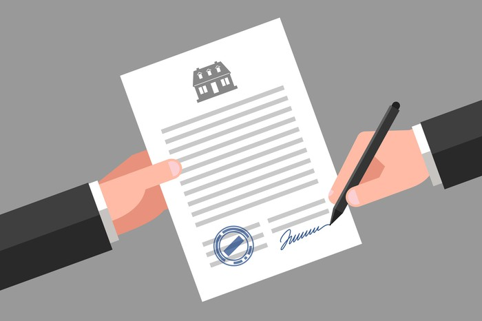 animated hand holds out a document with a picture of a house at the top  of it and another hand signs the bottom  of the document.