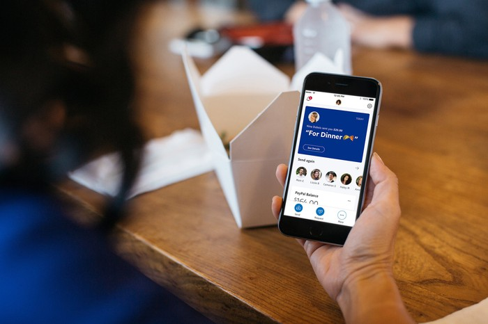 Person holding a smartphone with the PayPal app open.