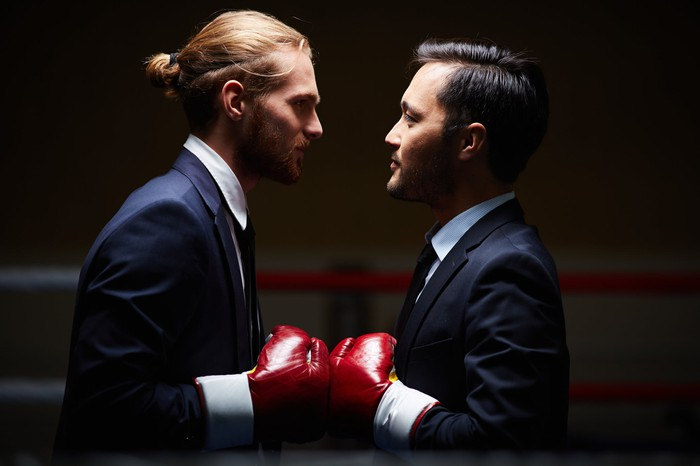 Two businessmen in boxing gloves.