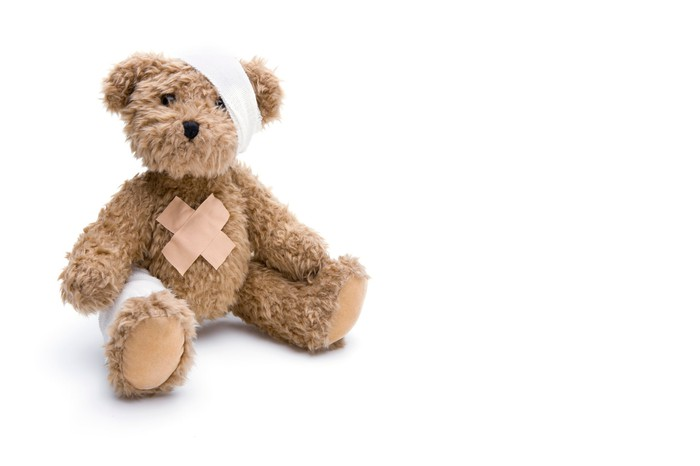 A teddy bear, covered in bandages and band-aids, sits in a plain white field.