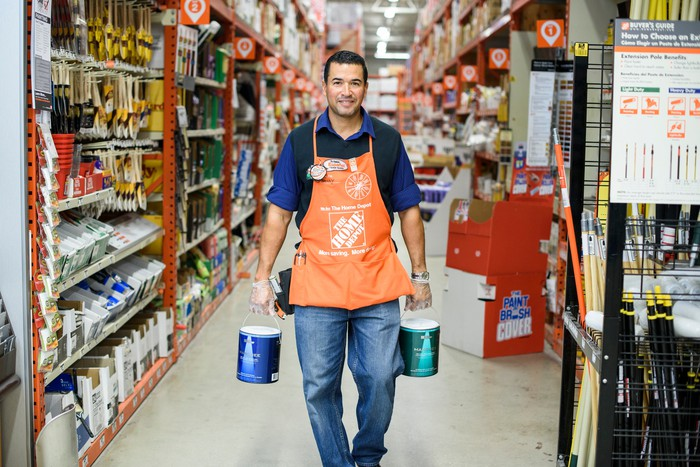 Home Depot associate carrying paint buckets down a store aisle