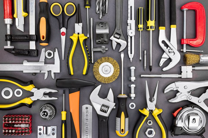 A collection of many tools on a gray surface