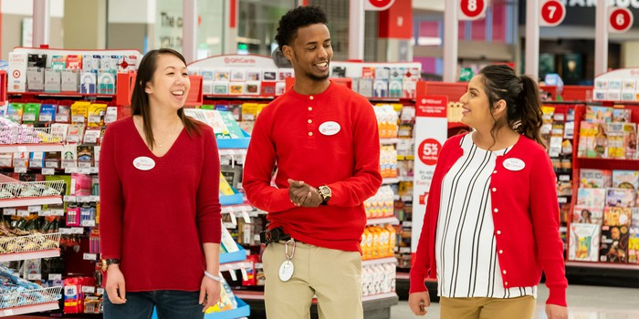 Three workers are seen in a Target store.